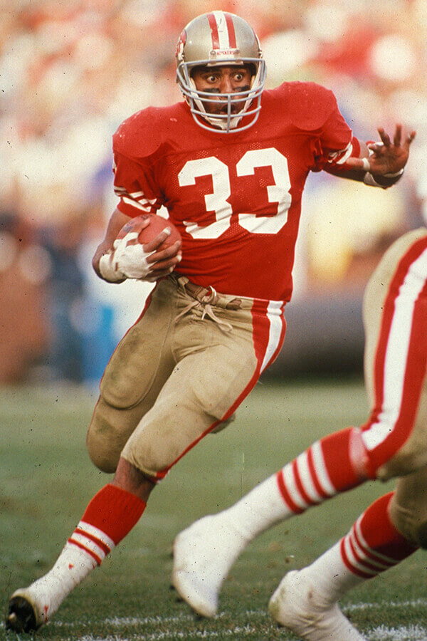 Roger Craig of the 49ers running with a football